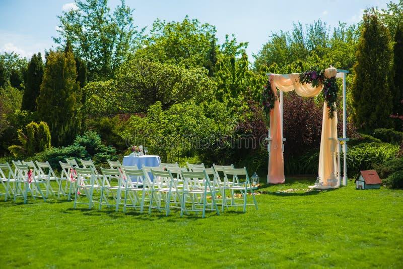Hochzeitsbogen und weiße Stühle im Garten stockbilder