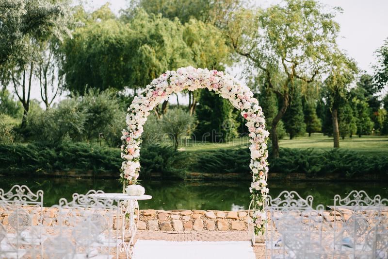 Hochzeitsbogen verziert mit den Blumen-, weißen und rosarosen Mit Weinlesestühlen auf einem Teichhintergrund im sonnigen Sommer lizenzfreie stockfotografie