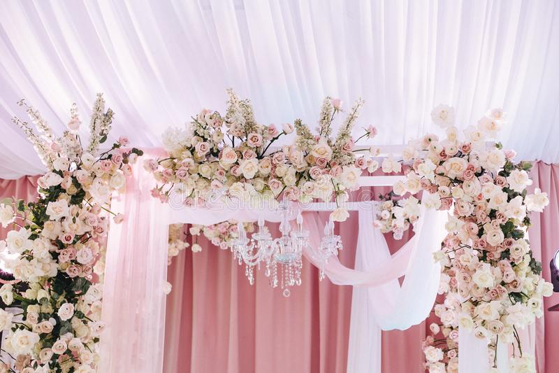 Hochzeitsbogen verziert mit weißem und rosa Stoff, Kristallleuchter und schönen Blumenzusammensetzungen von Rosen und von Ranuncu lizenzfreies stockbild