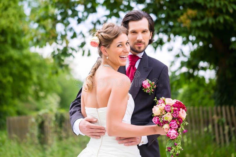 Hochzeitsbraut und -bräutigam mit Brautblumenstrauß lizenzfreie stockfotos