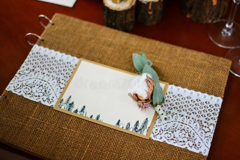 Hochzeitsdekor-Fotoalbum mit Ringen und Zweigbaumwolle stockbild
