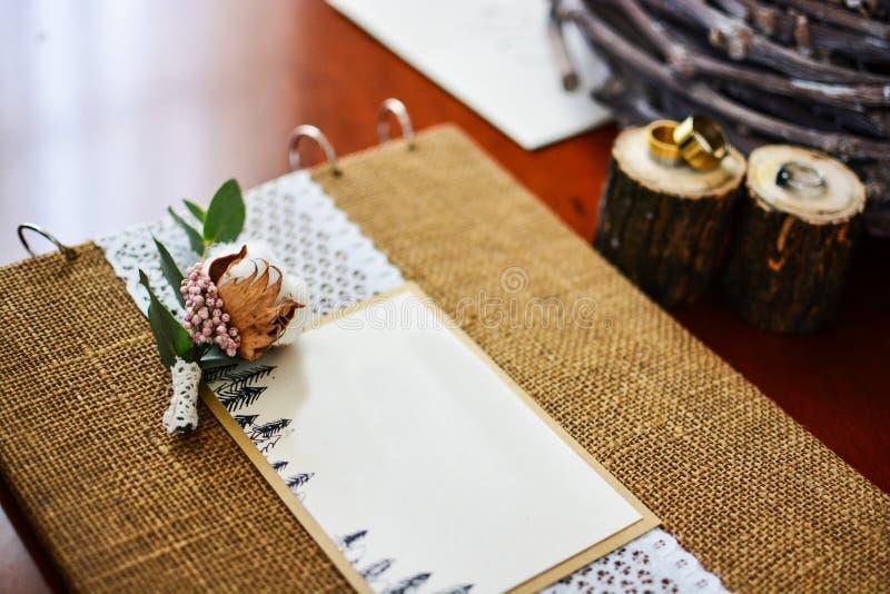 Hochzeitsdekor-Fotoalbum mit Ringen und Zweigbaumwolle lizenzfreies stockfoto