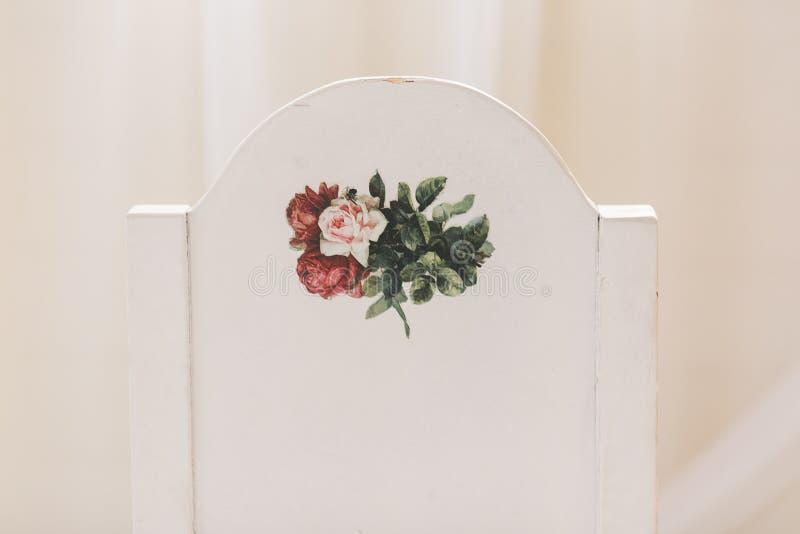 Hochzeitsdekor, hölzerner weißer Stuhl mit Rückseite des Blumendruckes an Naher Schuss lizenzfreies stockfoto