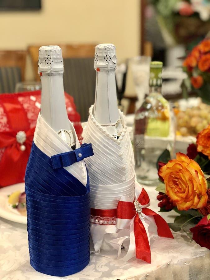 Hochzeitsdekor: orange und rote Rosen, Gläser, Flaschen, der Tischschmuckkerzen Jungvermählten, Präsidium stockfotografie