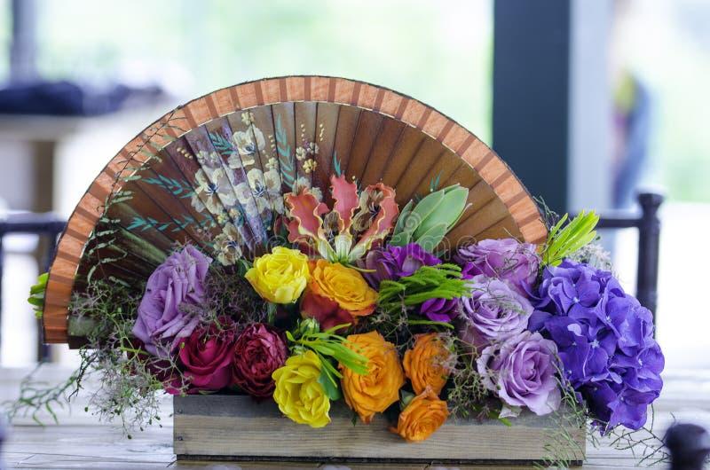 Hochzeitsdekoration mit Blumen und Handfan lizenzfreie stockfotos