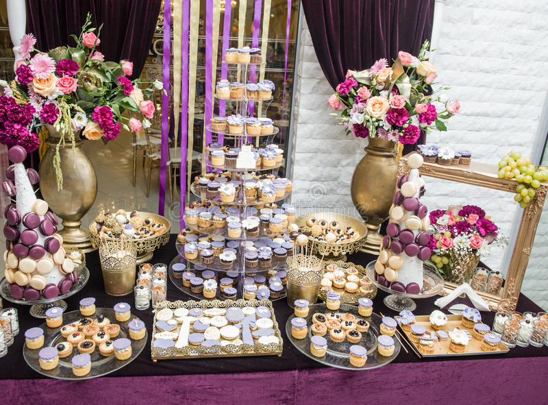 Hochzeitsdekoration mit mehrfarbigen Rosen im Vase, Pastell färbte kleine Kuchen, Meringen, Muffins und macarons lizenzfreie stockfotografie