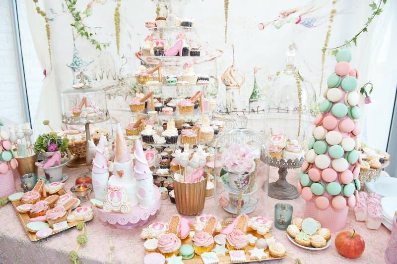 Hochzeitsdekoration mit Pastell färbte kleine Kuchen, Meringen, Muffins und macarons lizenzfreies stockbild