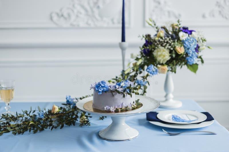 Hochzeitsdekorationen mit Kerzen, Kuchen und schönen Blumen lizenzfreies stockbild