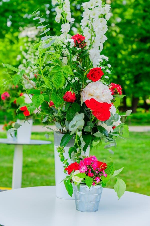 Hochzeitsdekorationsanordnung Schöne blühende Blumensträuße auf Tabelle lizenzfreie stockfotografie