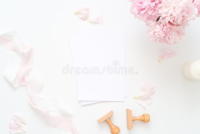 Hochzeitseinladung mit Leerseitenspott oben, Umschlag, Pfingstrosenblume mit den Blumenblättern, blaß - rosa Seidenband, stempelt stockbild