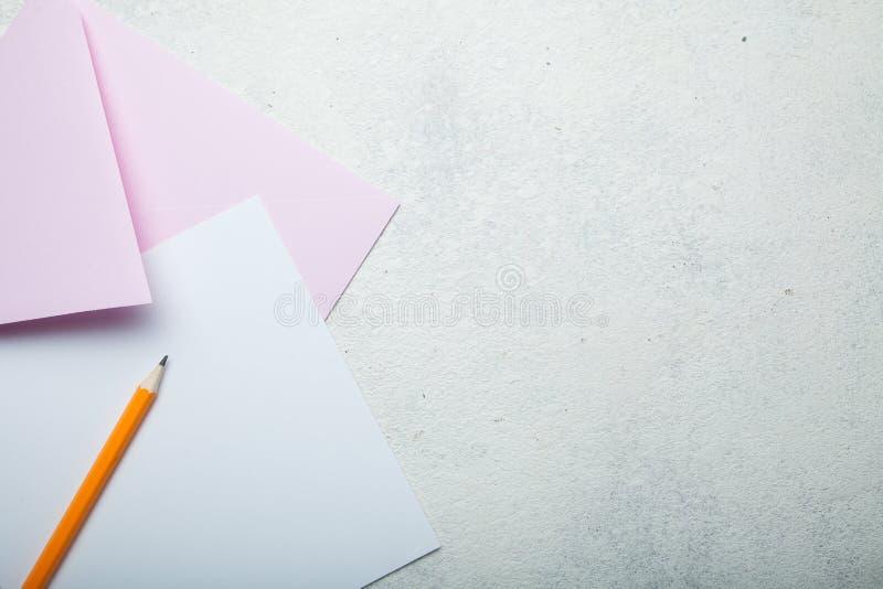 Hochzeitseinladung oder ein Feiertag Papier-, rosa Umschlag und Bleistift auf einem weißen Weinleseschreibtisch, Raum für Text lizenzfreie stockfotos