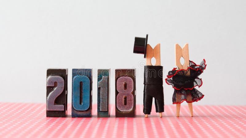 Hochzeitseinladungskarte des neuen Jahres 2018 Pflegen Sie schwarzen Anzugshut, schwarzes rotes Kleid der Braut Wäscheklammerchar lizenzfreie stockfotografie
