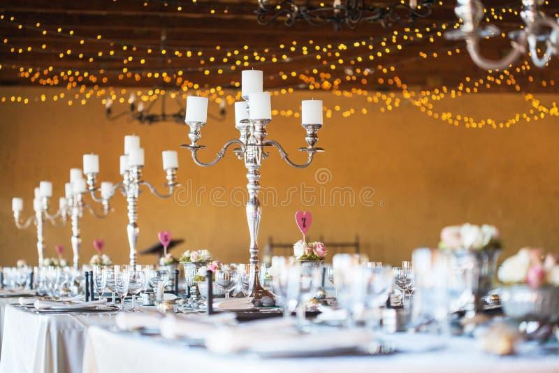 Hochzeitsempfanghalle mit Dekor einschließlich Kerzen, Tischbesteck und stockfotografie