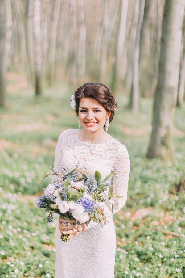 Hochzeitsfoto des schönen Brautmädchens mit den roten Lippen und dem dunklen gewellten Haar, Porträt der Schönheit im Freien Attr stockfotografie