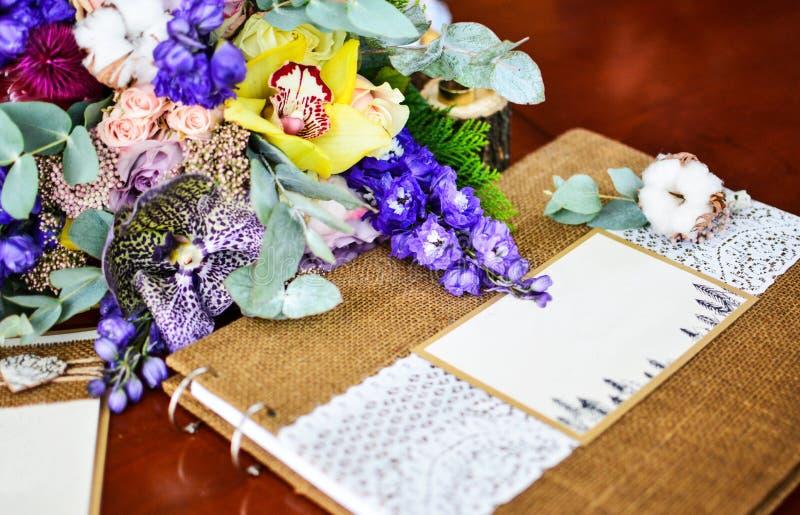 Hochzeitsfotoalbum-Blumenstraußeukalyptusbaumwolle und andere Blumen lizenzfreies stockbild