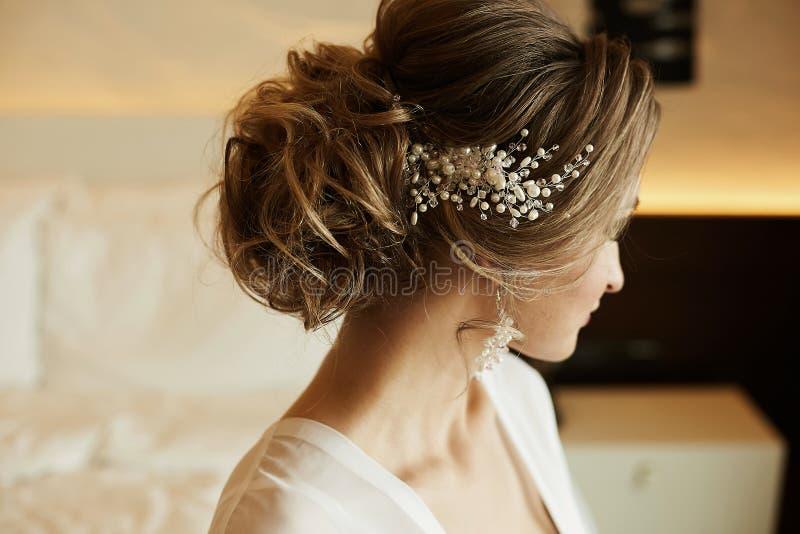 Hochzeitsfrisur des schönen und modernen braunhaarigen vorbildlichen Mädchens in einem Spitzekleid, mit Ohrringen und Schmuck in  lizenzfreie stockfotos
