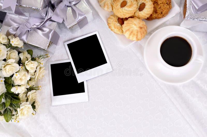 Hochzeitsgeschenke und -fotos mit Kaffee und Keksen stockfotos