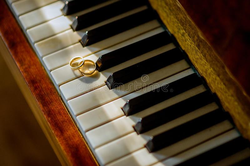 Hochzeitsgoldringe auf dem Klavier nahaufnahme Zu küssen Mann und Frau ungefähr Braut- und Bräutigamzubehör lizenzfreie stockfotos