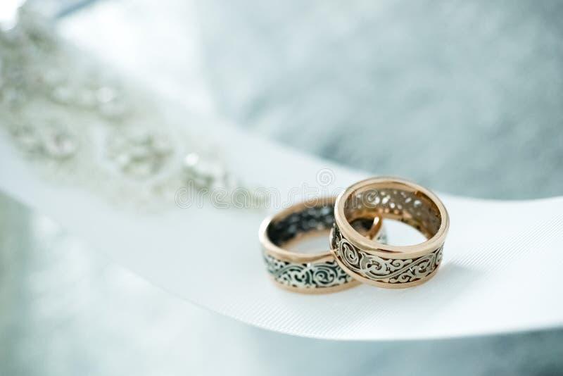 Hochzeitsgoldringe auf weißem Band lizenzfreie stockfotografie