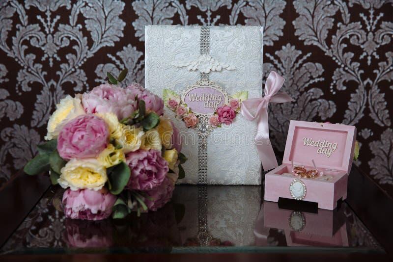 Hochzeitsgoldringe und Blumenstrauß von Blumen auf einem dunklen Holztisch Konzeptheirat lizenzfreies stockfoto