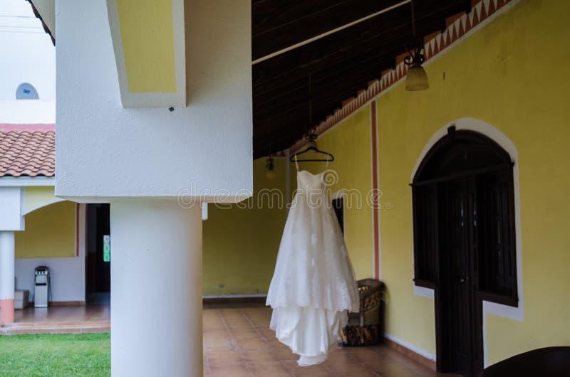 Hochzeitskleid, das über dem Korridor eines Hotelinnenraums, hölzerne Bars auf dem Dach eines Hotelkorridors hängt lizenzfreies stockbild