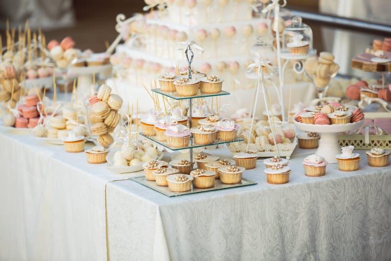 Hochzeitskleine kuchen auf der Hochzeitstafel stockbilder