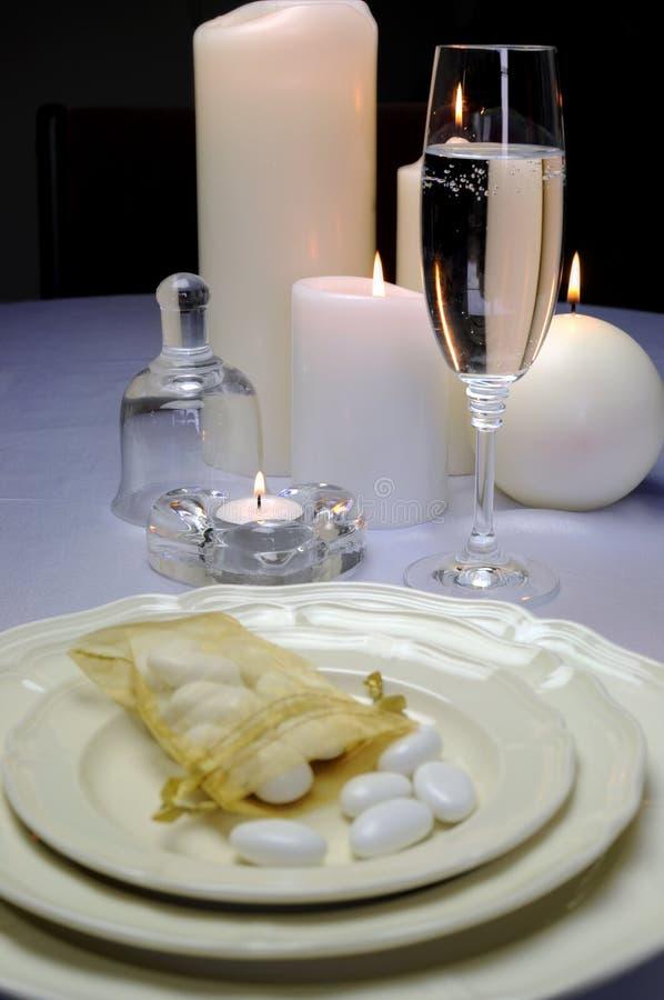 Hochzeitsmahl, das Gedeck mit Zuckermandeln auf fina Porzellan mit Sektkelch speist stockbild