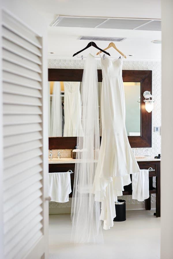 Hochzeitsmeerjungfraukleid und langer Schleier, die im Reinraum, Reflexion im Spiegel hängen stockfoto