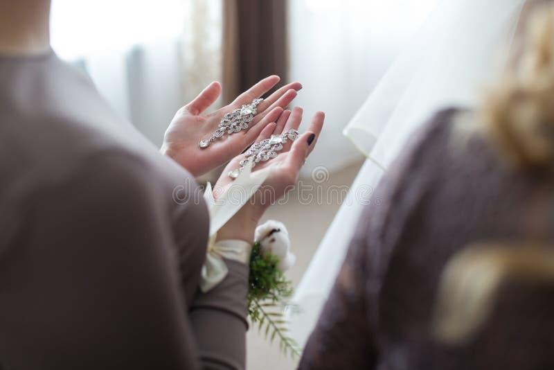 Hochzeitsohrringe auf einer weiblichen Hand stockfotografie