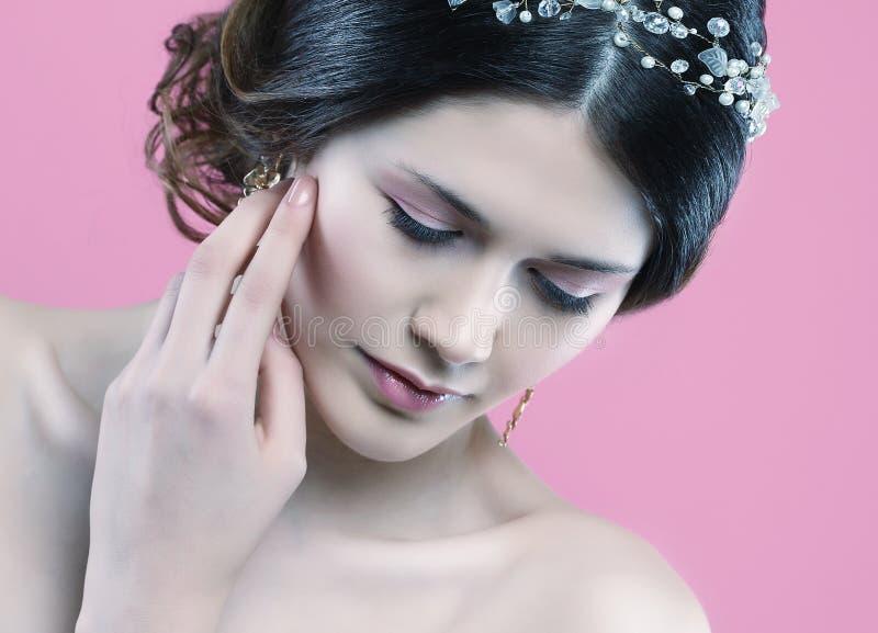 Hochzeitsohrringe auf einer weiblichen Hand, nimmt sie die Ohrringe, tr?gt Ohrringe lizenzfreies stockfoto