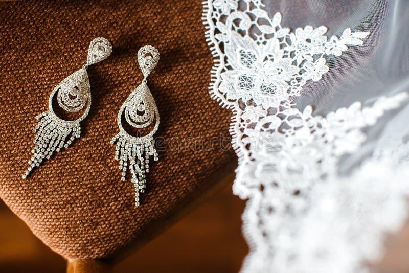 Hochzeitsohrringe und -schleier auf dem Stuhl stockbild