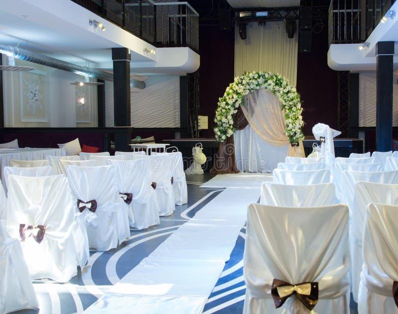 Hochzeitsort mit einer Brautlaube und Stühlen stockbilder