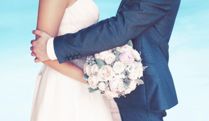 Hochzeitspaar, Blumenstrauß von Pfingstrosenblumen, Bräutigam umarmt reizende Braut stockfotografie
