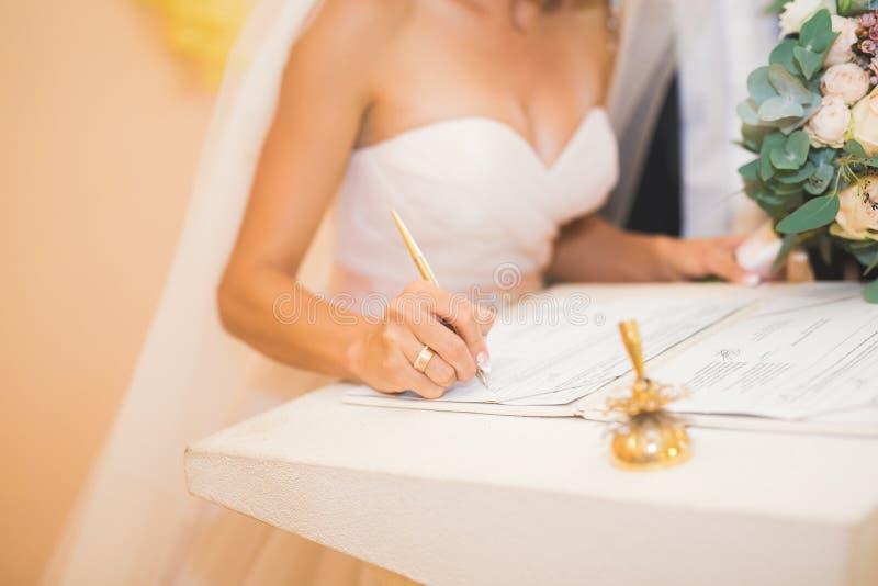 Hochzeitspaarbraut und -bräutigam, die ihre Unterschriften lassen lizenzfreie stockfotografie