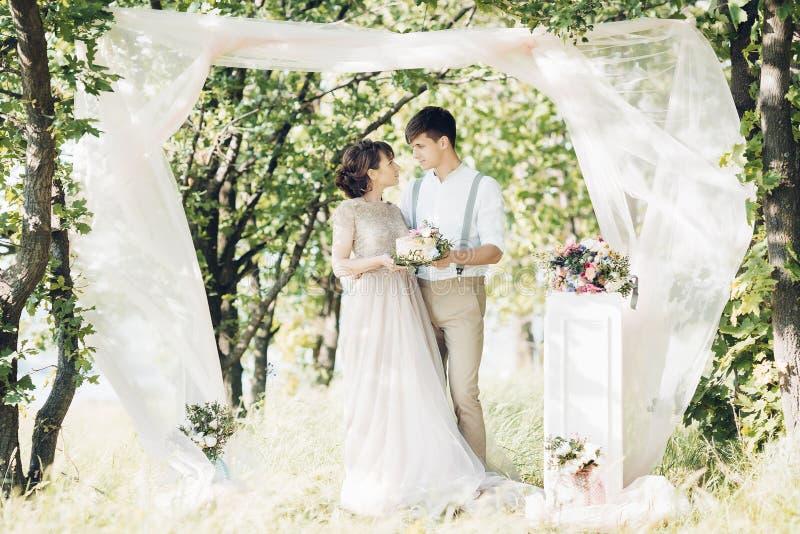Hochzeitspaare auf Natur Braut und Bräutigam mit Kuchen an der Hochzeit stockfotografie