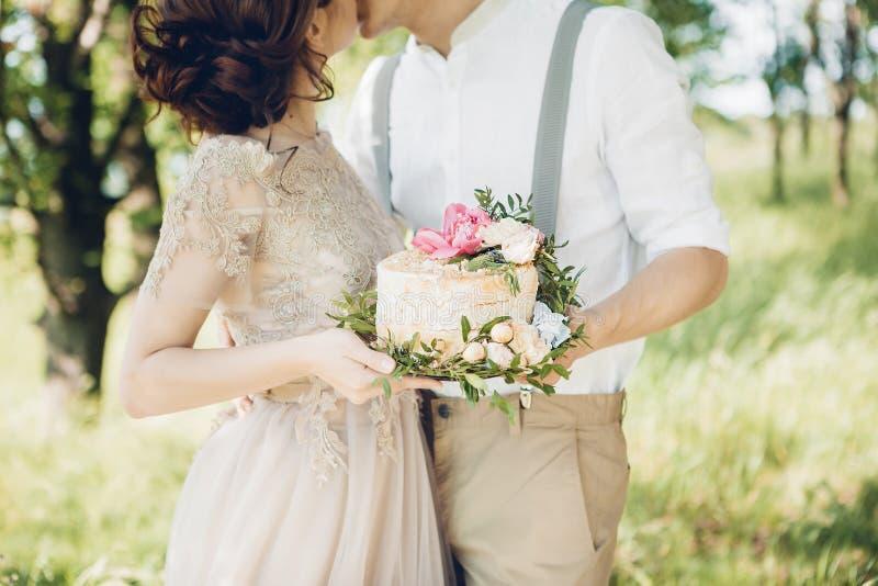 Hochzeitspaare auf Natur die Braut und der Bräutigam mit Kuchen an der Hochzeit lizenzfreie stockfotos