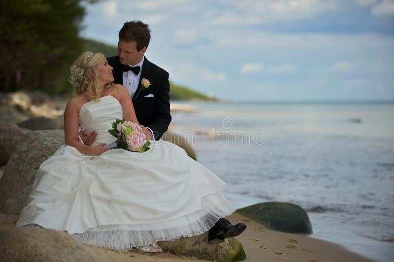 Hochzeitspaare auf steinigem Strand stockbild