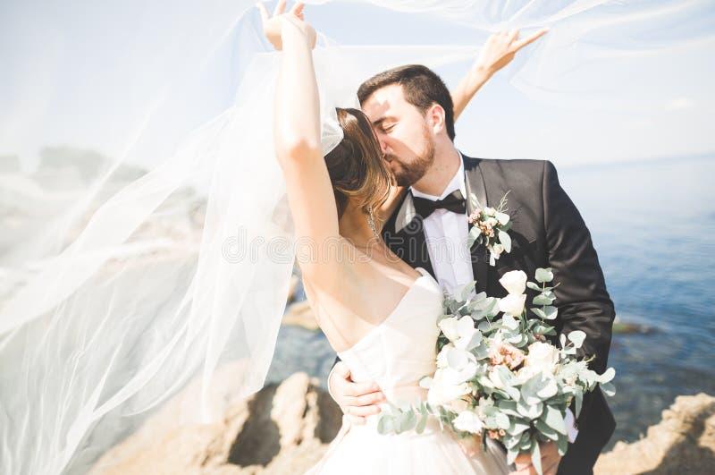 Hochzeitspaare, Bräutigam, Braut mit dem Blumenstrauß, der nahe Meer aufwirft und blauer Himmel stockbild