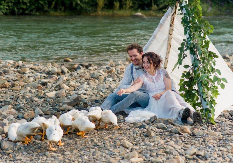 Hochzeitspaare, -bräutigam und -braut auf dem Hintergrund eines Gebirgsstromes lizenzfreie stockfotos