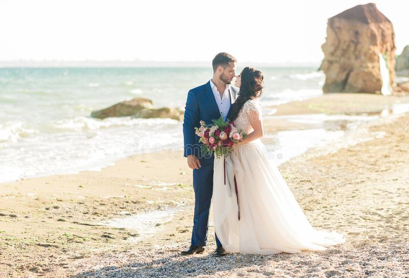 Hochzeitspaare, -bräutigam und -braut im Hochzeitskleid nahe dem Meer an der Küste lizenzfreie stockfotos