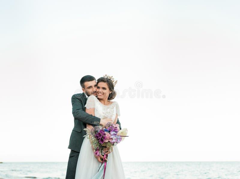 Hochzeitspaare, -br?utigam und -braut im Hochzeitskleid nahe dem Meer an der K?ste stockfotos