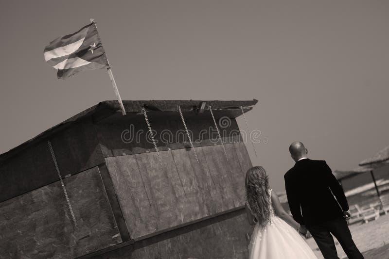 Hochzeitspaare, die auf einen Strand in Kuba gehen lizenzfreie stockbilder