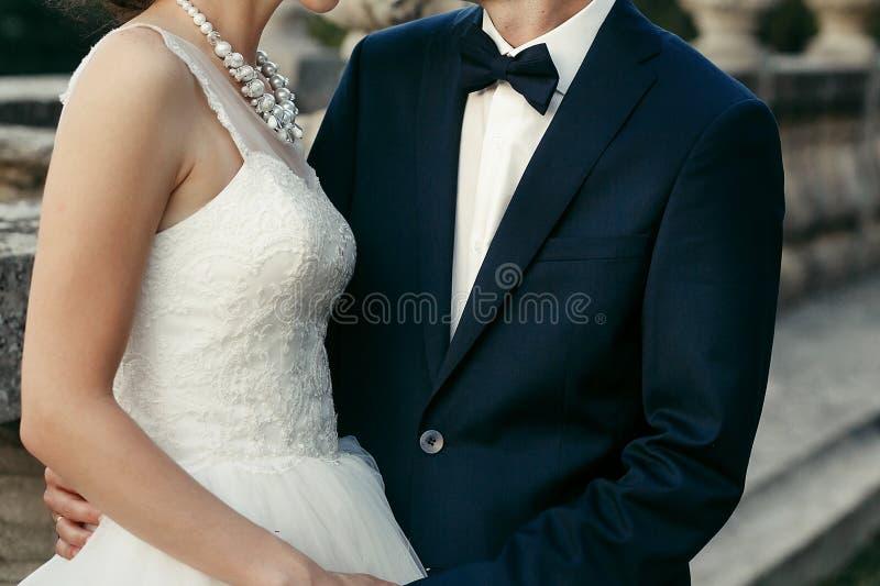 Hochzeitspaare, die auf Hintergrund des alten Schlosses umarmen elegantes brid stockfoto