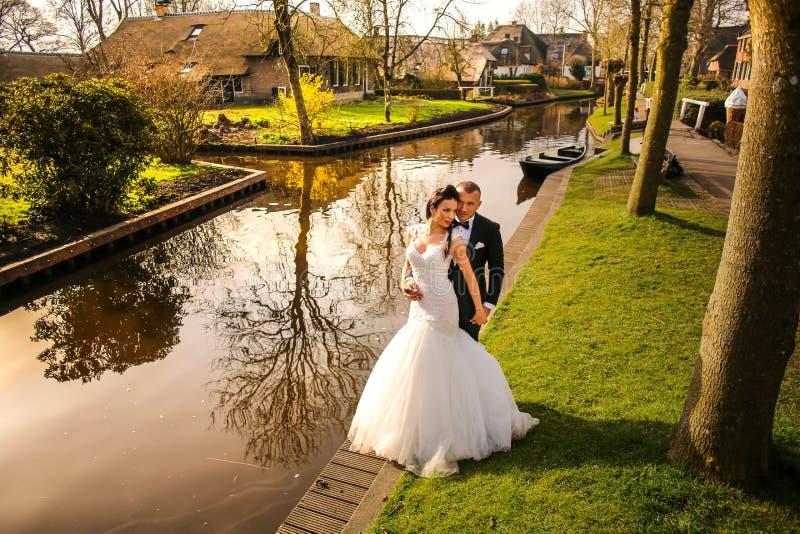 Hochzeitspaare, die nahe Fluss aufwerfen stockfoto