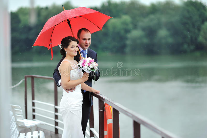 Hochzeitspaare an einem regnerischen Tag lizenzfreie stockfotos