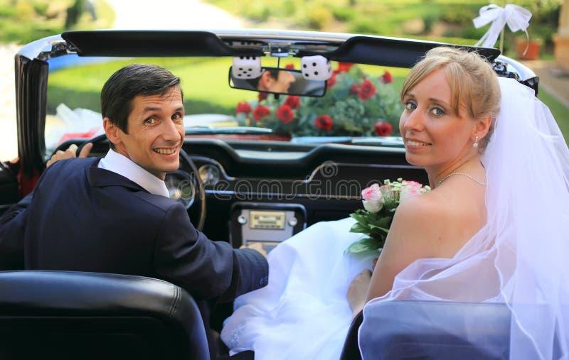 Hochzeitspaare im Auto lizenzfreie stockbilder