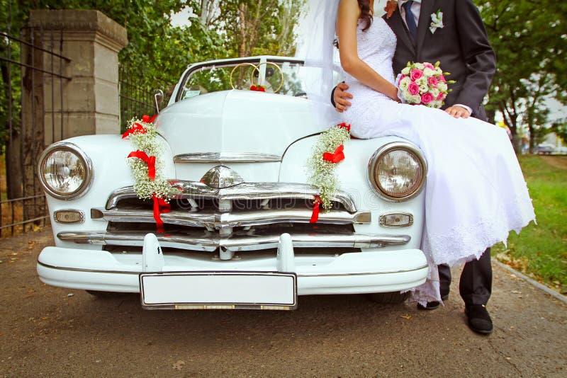 Hochzeitspaare mit Hochzeitsauto lizenzfreies stockbild