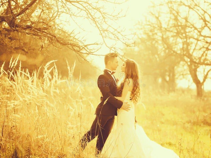 Hochzeitspaargehen im Freien stockfotos