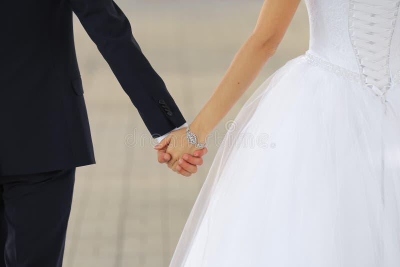 Hochzeitspaarhändchenhalten schließt oben stockfotos