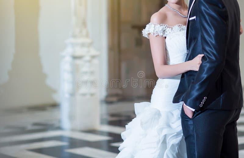 Hochzeitspaarhändchenhalten und -c$umarmen Bräutigam umarmt Braut lizenzfreies stockbild